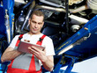 Motor mechanic works under the service lift with his touchpad
