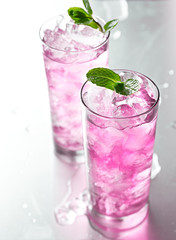 pink cocktail with mint garnish.