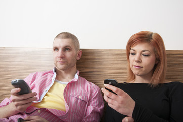 Young couple sitting on hotel bed using mobile phones
