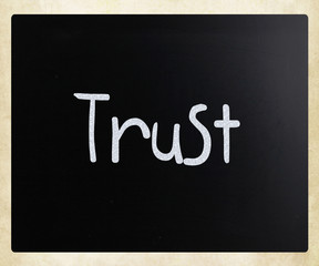 "The word ""Trust"" handwritten with white chalk on a blackboard"