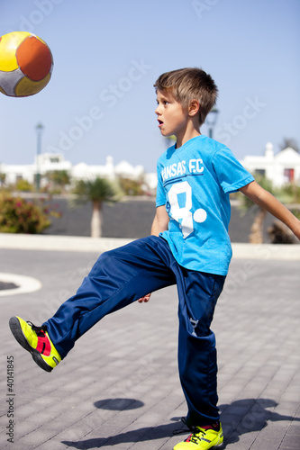A boy playing football in the street