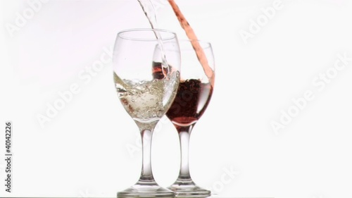 Red and white wine poured in super slow motion