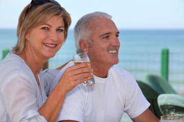 mature couple having fresh beer at cafe near sea
