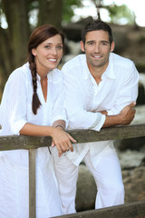 Couple in white leaning on a country fence