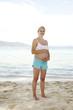 junge schwangere frau macht yoga am strand