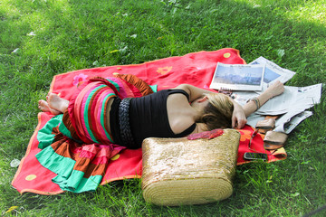 Beautiful women is napping on grass in a park