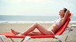 Sexy woman in bikini sunbathing on sunbed by the sea