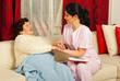 Nurse comforting sick elderly woman