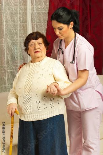 Nurse helping sick senior home