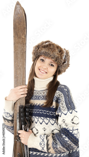 smiling teenage girl in winter hat with old wooden skis