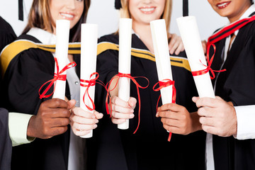 group of multiracial graduates holding certificates