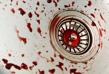 a lot of fake blood drops in metal kitchen sink