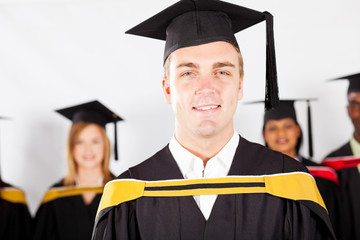 happy male college graduate with classmates at graduation