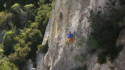 Male athlete training and climbing on rocks