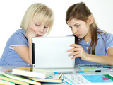 Two cute girlfriends learning with books and touchpad
