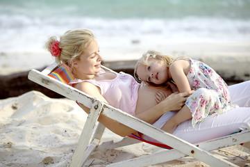 junge schwangere mutter sitzt mit ihrer tochter im liegestuhl am