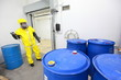 worker in uniform dealing with barrels of toxic substance