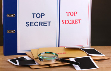 Envelopes and folders with top secret stamp and magnifying