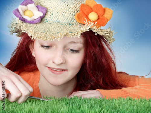 Teenager with flower hat cuts synthetic turf with nail scissors