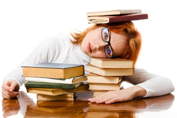 Beautiful red-haired girl in glasses reads book.