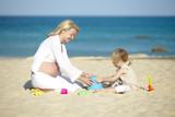 schwangere mutter spielt sand mit ihrer tochter