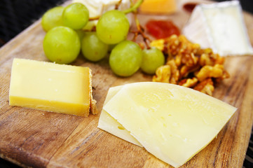 gourmet cheese plate with fruit and walnuts