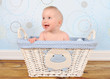 adorable baby boy sitting in blue wicker basket