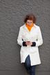 Frau an Wand schaut auf Handy