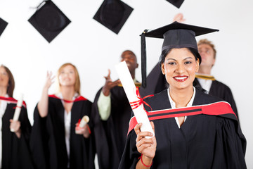 happy female indian graduate at graduation with classmates