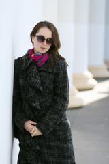 Smiling woman wearing coat outdoor. Springtime