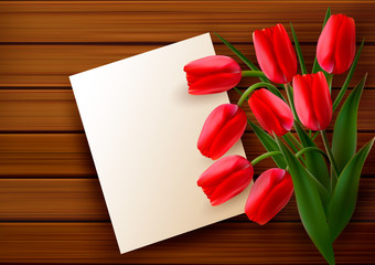 Red tulips and blank card  on old wooden board.