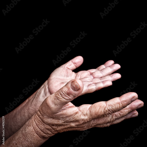 Wrinkled old hands isolated on black