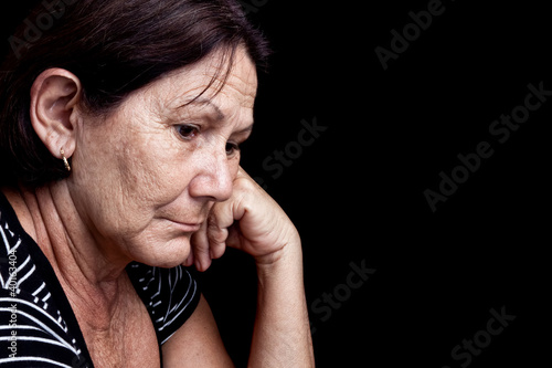 Sad and worried old woman isolated on black