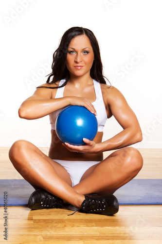 Blue fitness ball in girl's hands