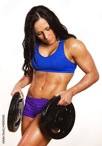 Sportswoman is holding weights