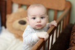 Pensive baby in cot