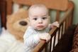 Pensive baby in cot
