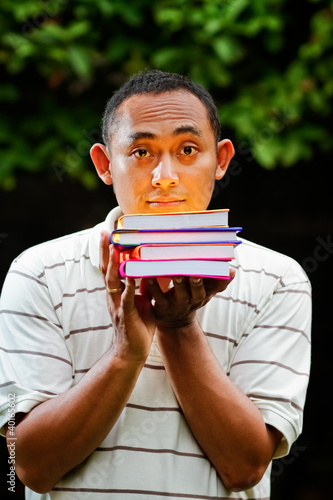asian young man with stack of books on hands