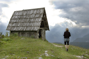 Woman exploring abandoned mountain cottage