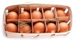 Eggs with a straw in a wooden basket on a white background.