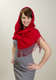 Young smiling woman in a red scarf. On grey background.