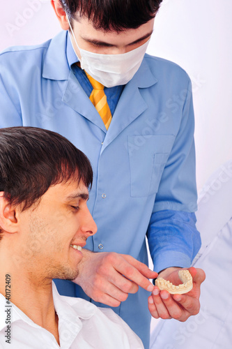 Patient in a dentist office looking at plaster cast of his teeth