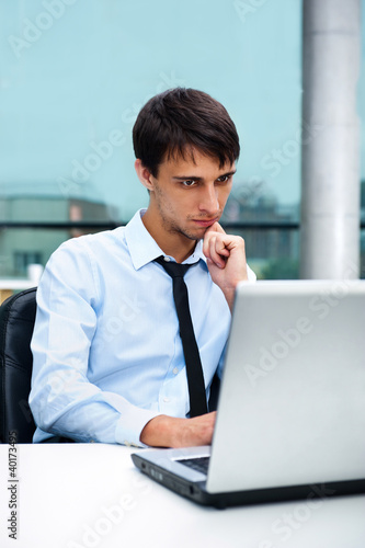 A young man sitting in front of a laptop at office