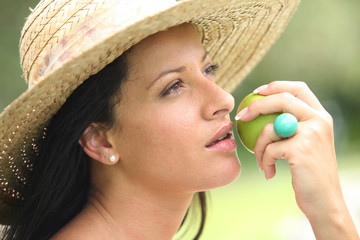 Woman in a straw hat about to bite an apple