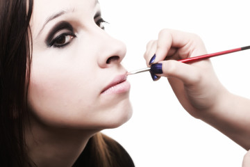 beautiful young woman applying lips make-up zone