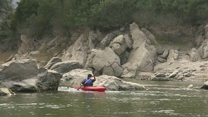 adult man on red canoe paddling for fun among rocks