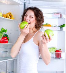 Beautiful Young Woman near the Refrigerator with healthy food