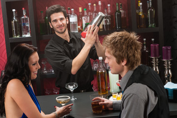 Bartender shaking cocktail friends having drink
