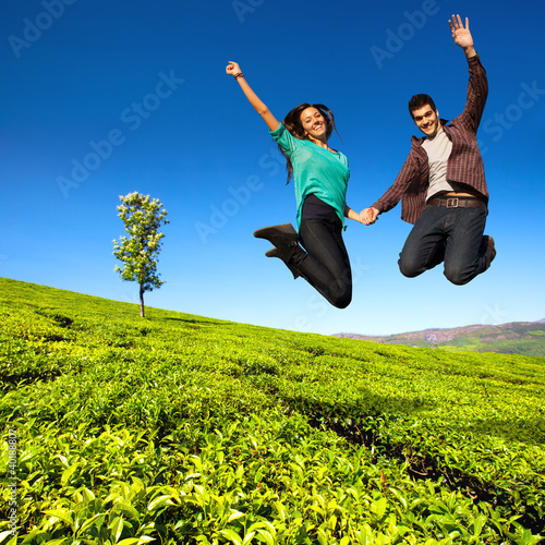 Jumping couple in green field.