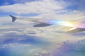 Flugzeug-Flügel mit Lichtreflex über den Wolken